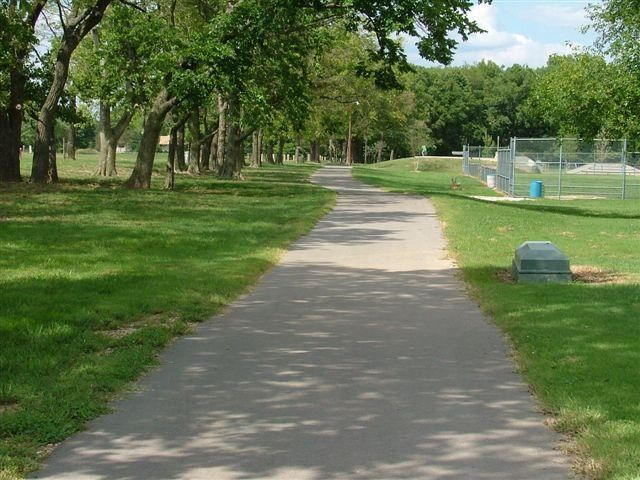 Paved trail with lawn and tress and fields