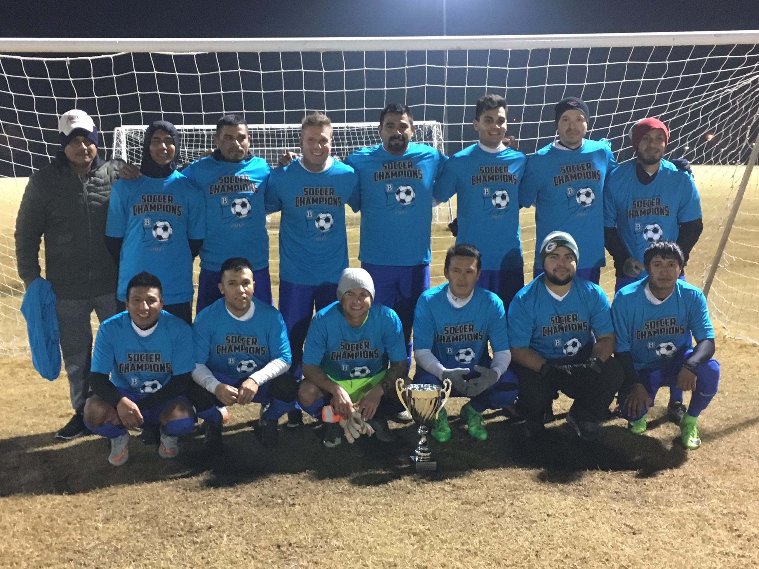 Gold Division team in blue jerseys in front of soccer goal