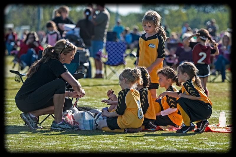 Coach talks to young girls soccer team in yellow jerseys