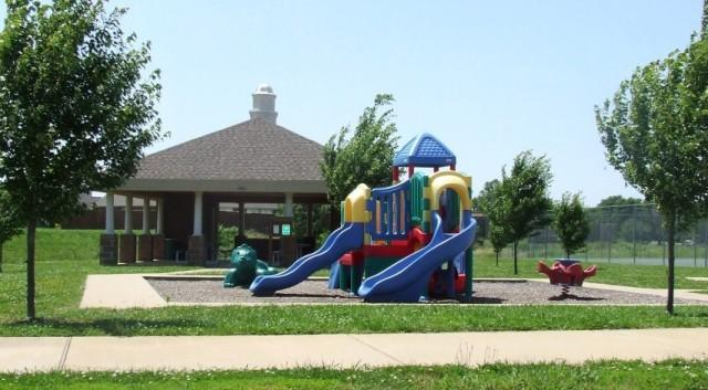 Wildwood Park image of plastic playground with pavilion in background and grass with sidewalk