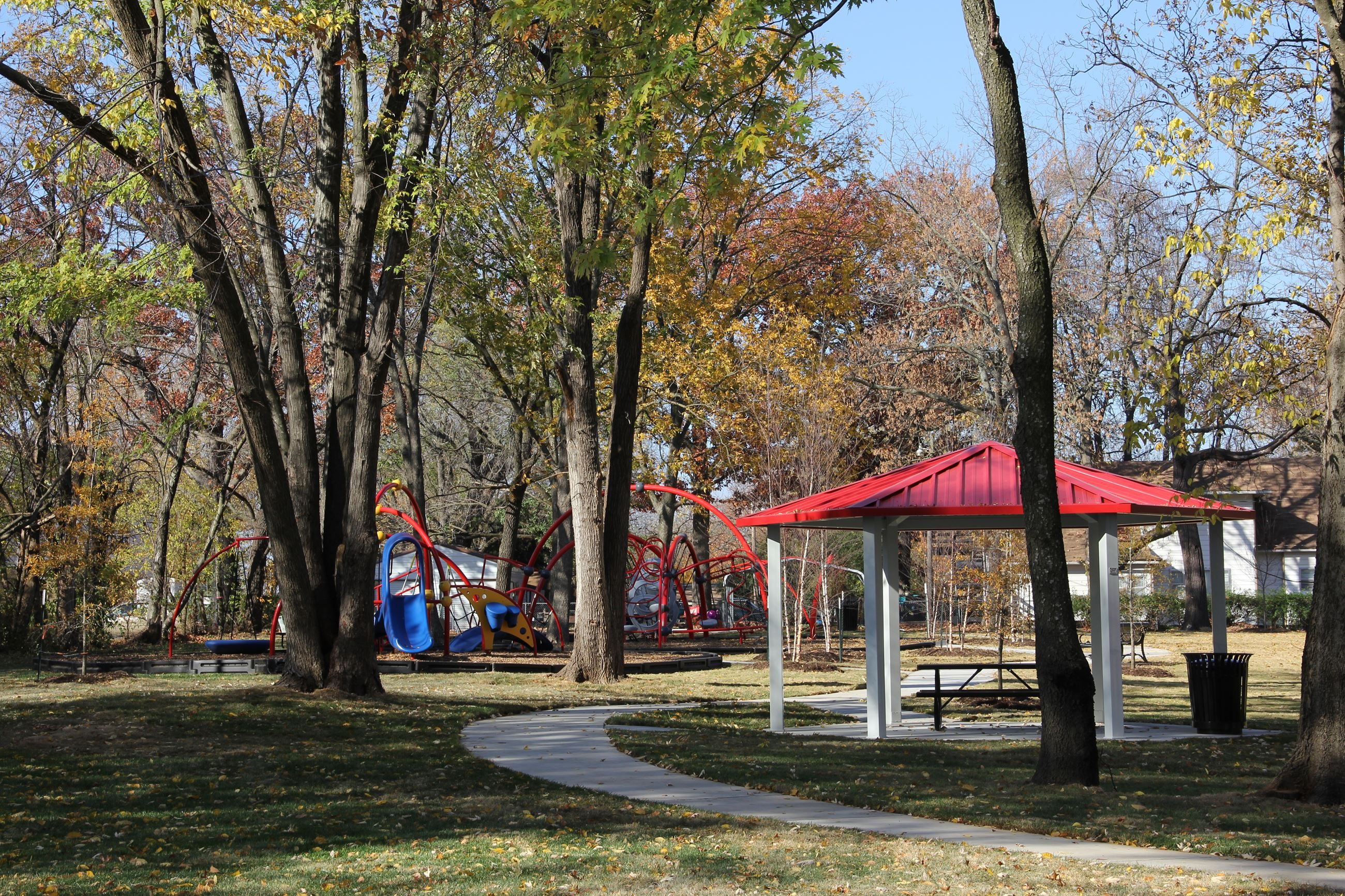 Austin-Baggett Park Image of park with sidewalk and playgrounds with trees
