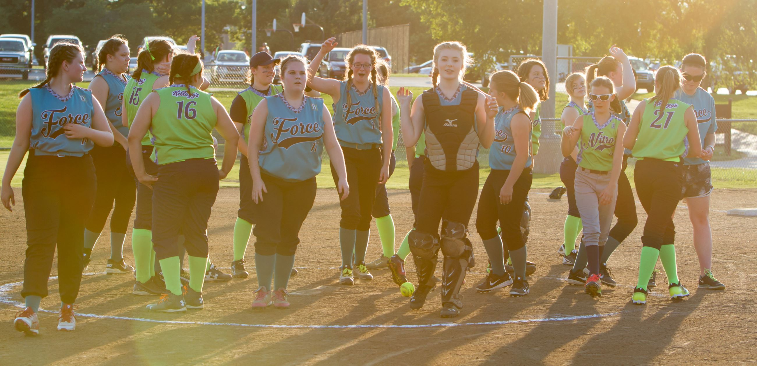 Two girls softball teams mingle on field